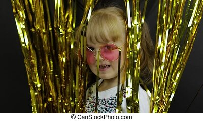 Happy child jumping, playing, fooling around in shiny foil fringe golden curtain. Little blonde girl