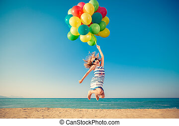 Happy child jumping with colorful balloons on sandy beach. ...