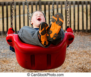 Happy child laughing while swinging at playground