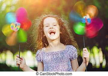 Happy child leisure in summer outdoor. Laughing girl holding...