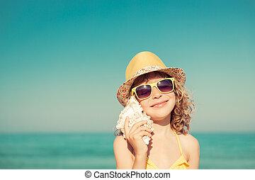 Happy child listen seashell on the beach