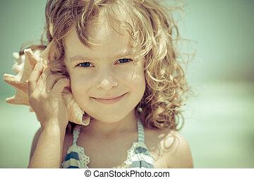 Happy child listen to seashell at the beach