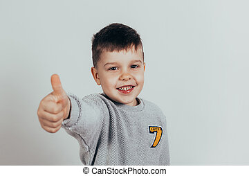 Happy child, little boy showing thumbs up gesture in gray sweater against gray background. Space for your text.
