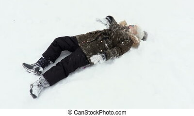 Happy child lying and playing in the snow
