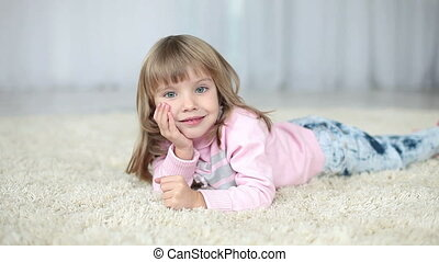 Happy child lying on a carpet.
