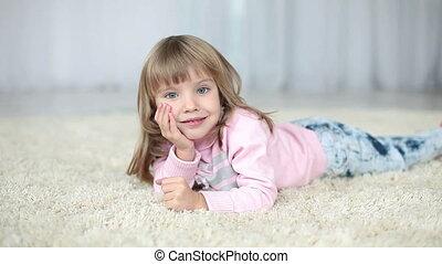 Happy child lying on a carpet.