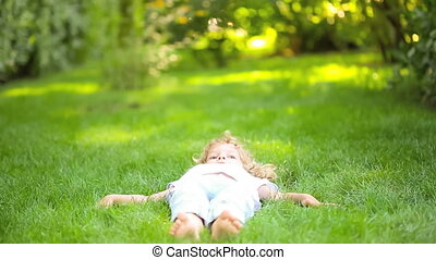 Happy child lying on green grass