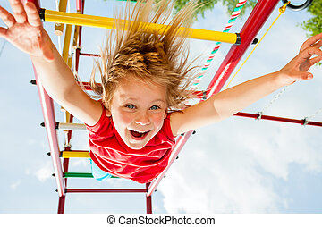 Happy child on a jungle gym