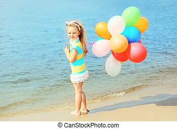 Happy child on beach with colorful balloons near sea summer