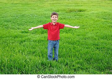 Happy child on green grass background