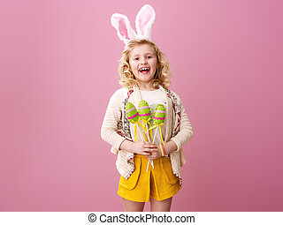 happy child on pink background with handmade Easter eggs -...