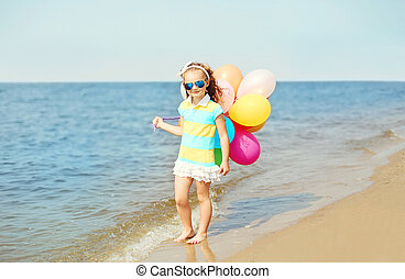 Happy child on summer beach playing with colorful balloons near sea