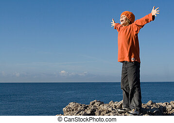 happy child on vacation shouting or singing with arms outstretched