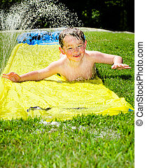 Happy child on water slide to cool off on hot day during...
