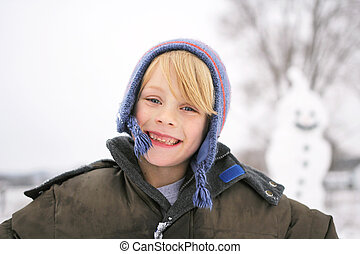 Happy Child Outside playing in the Snow after Building Snowman