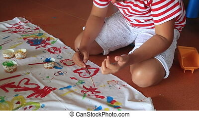Happy child painting on a fabric