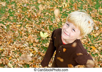 Happy Child Play in Falling Leaves
