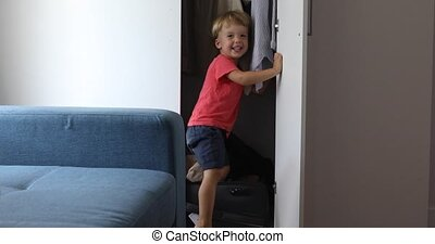Happy child playing closet suitcase - Little child playing...