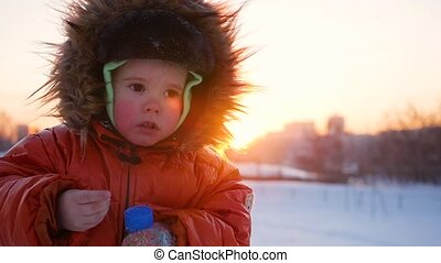 happy child playing in the park on a sunny winter day. Snow winter landscape. on open air
