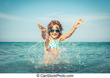 Happy child playing in the sea