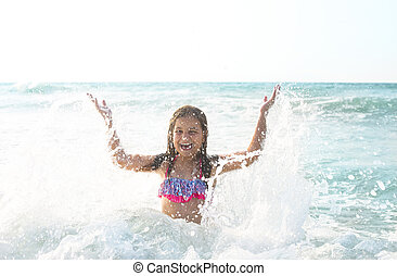 Happy child playing outdoors. Kid having fun in the sea. Summer vacation and travel concept.