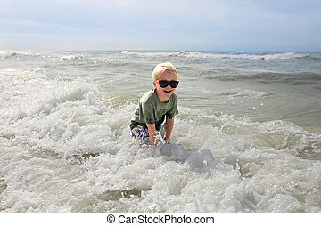 Happy Child Playing Outside in the Ocean Waves