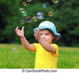 Happy child playing with bubbles the hands on summer green...