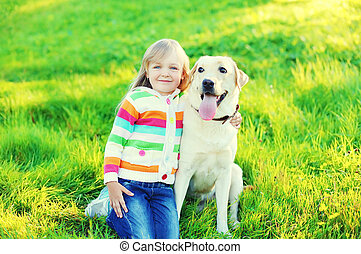 Happy child playing with labrador retriever dog on grass in summer day