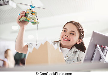 Happy child playing with modern helicopter