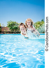 Happy child playing with mother in pool