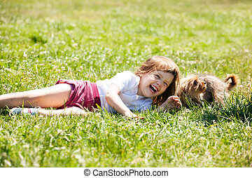 happy child playing with puppy at meadow in summer