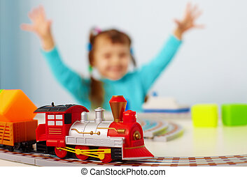 Happy child playing with railway - A happy child playing...