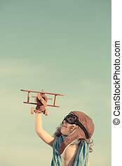 Happy child playing with toy airplane against summer sky