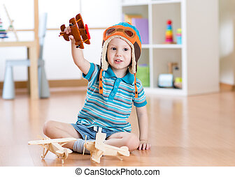 Happy child playing with toy airplane at home