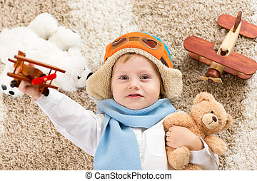 Happy child playing with toy airplane. Kid boy lying on fluffy carpet