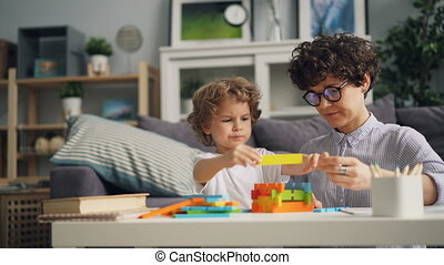 Happy child playing with wooden blocks building with mom at home focused on game