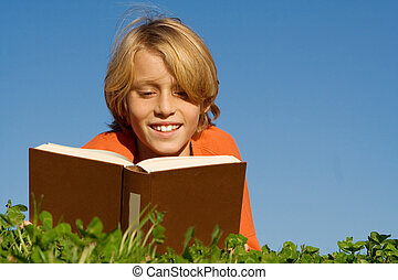 happy child, reading book outdoors,