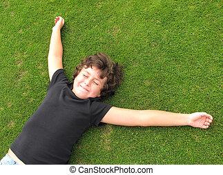 Happy child resting on grass