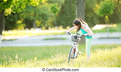 Happy child riding a bike in the city park at summer warm day.