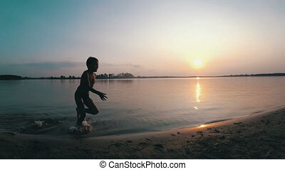 Happy Child Runs Along the Beach at Sunset. Slow Motion