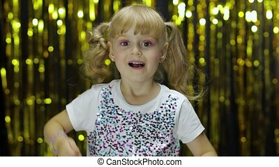 Happy child show thumbs up, smiling, looking at camera. Little fun blonde kid teen girl 4-5 years old in shiny white t-shirt posing isolated on background with foil fringe golden curtain in studio
