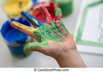 Happy child showing off a colourful hand