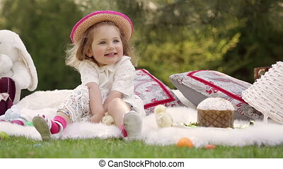 Happy child sits on a meadow around Easter decoration