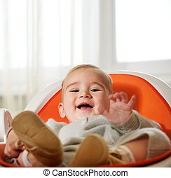 Happy child sitting on a chair