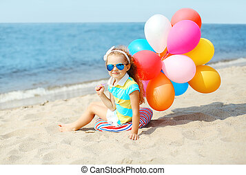 Happy child sitting on summer beach with colorful balloons near sea