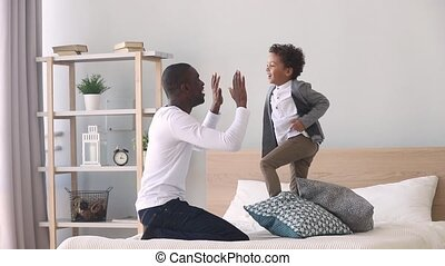 Happy child son jumping playing with black father on bed