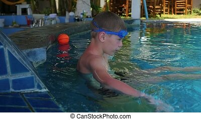 Happy child swims with pleasure in the pool