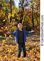 Happy child throws up leaves in autumn park