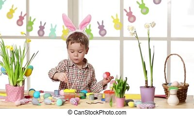 Happy child wearing bunny ears painting eggs on Easter day....