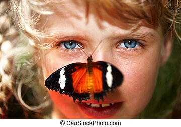 Happy child with butterfly on neck. Nature.